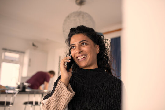 Happy woman talking on smart phone at home