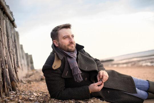 Serene man in winter coat relaxing on beach