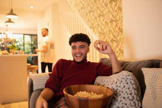 Happy young man with popcorn watching TV on living room sofa