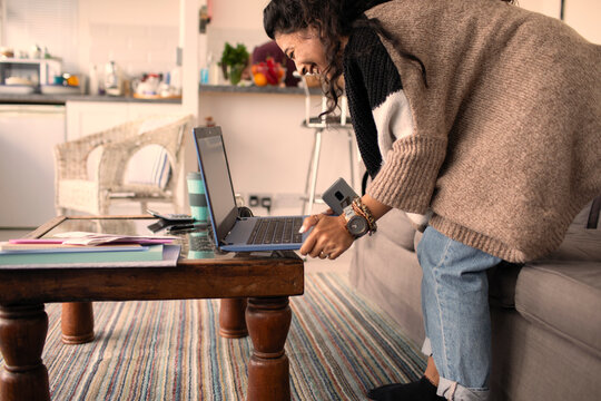Happy woman working from home at laptop in living room