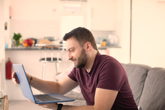Man working from home at laptop on sofa