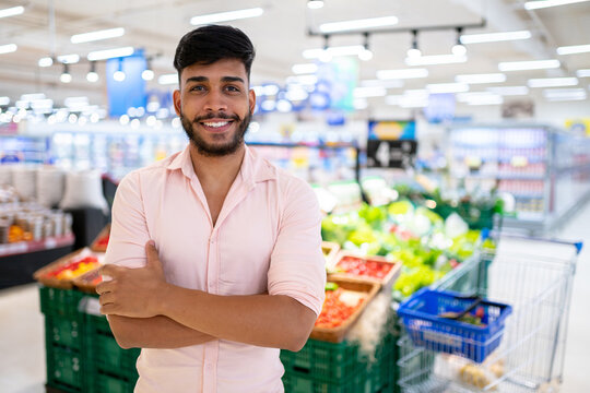 Latin American at the supermarket. Smiling man with arms crossed and looking at camera