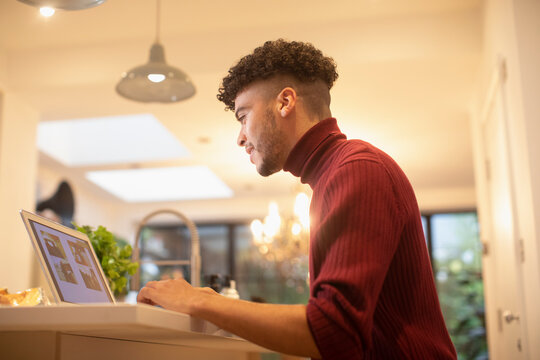 Young man working from home at laptop in kitchen