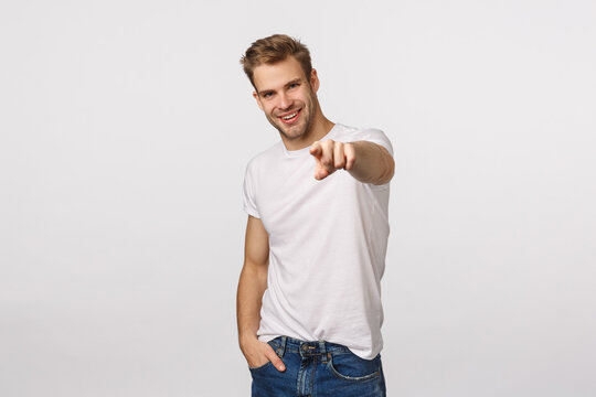 We need you, come here. Attractive and assertive, confident sassy blond guy looking for employees, pointing finger at camera and smiling pleased, found excellent person for company vacancy