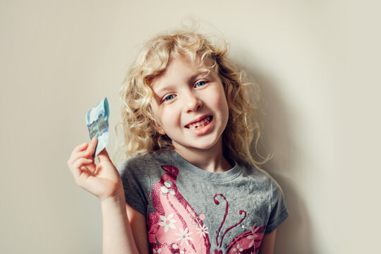 Caucasian blonde girl showing her missing tooth in mouth and holding money from tooth fairy. Proud child kid showing lost tooth. Growing up stage and adolescence.
