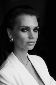 Black and white fashion portrait of a beautiful luxurious woman in a white jacket, professional makeup and glamorous accessories