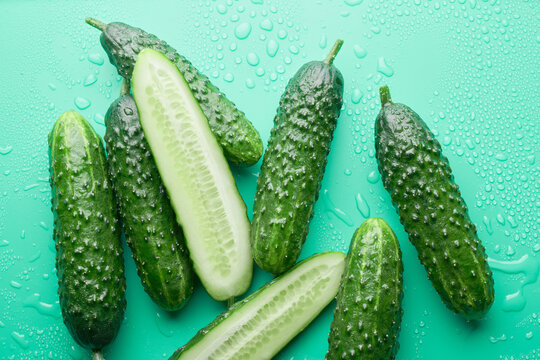 Set of fresh whole and sliced cucumbers on a green background with water drops. Garden cucumber wallpaper backdrop design