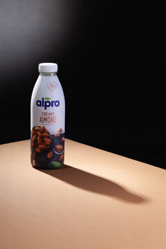 Alpro almond drink and shadow on the brown table.