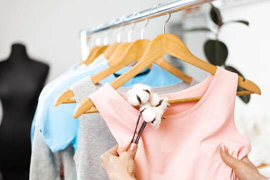 Organic cotton clothing. Hanger with dresses in the store. Sustainable fashion, caring for the environment.