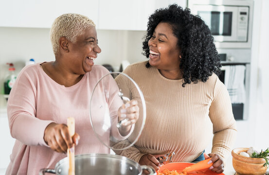 Happy Afro mother and daughter preparing lunch together in modern house kitchen - Food and parents unity concept