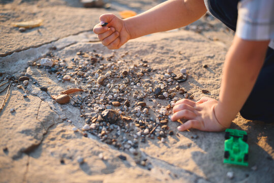 boy playing with stones on ground