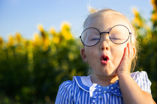 Little girl in a dress and glasses on the background of a sunflower field. Emotional face