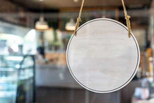 blank vintage wooden sign board hanging on glass door in modern cafe restaurant, copy space for text advertising, advertisement marketing and small business owner concept