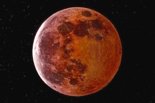 The picture shows the blood moon with stars over the city of Bottrop in North Rhine-Westphalia with a clear night sky.