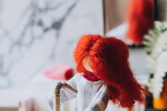 Red headed doll syanding in a bathroom at a sink. Room for copy.