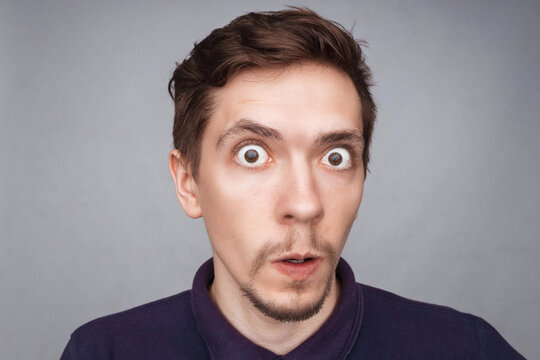 Emotions concept. Portrait of shocked male with small beard says wow, looks bugged eyes and rounded mouth, being amazed to see something unexpected. Terrified guy with surprised expression.