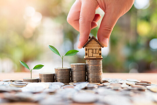 house model on money coins saving for concept investment mortgage finance and home loan refinance