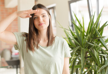 Fototapeta pretty woman greeting the camera with a military salute in an act of honor and patriotism, showing respect obraz