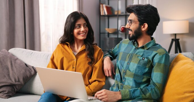 Portrait of young Hindu joyful married couple sitting on sofa in cozy living room browsing online on laptop computer surfing internet choosing something, e-commerce, wife and husband concept