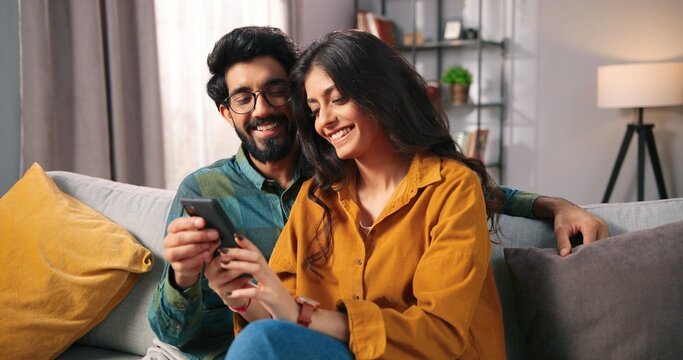 Portrait of cheerful positive young lovely couple smiling spending time together at home sitting on sofa typing on smartphone, searching internet using social network app on cellphone, family concept