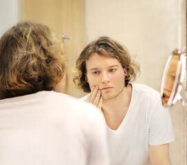 Fototapeta young man looking in the mirror,combing his hair,looking at problems on face..