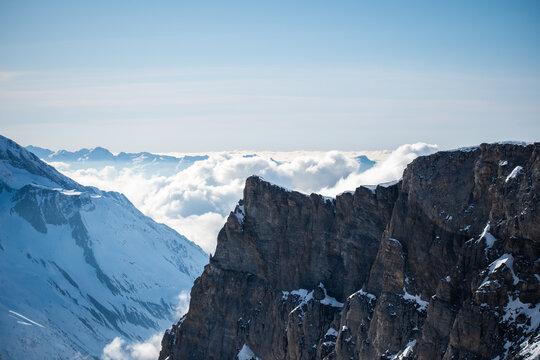 Montagnes à Tignes avec des nuages  au loin et une montagne au premier plan.