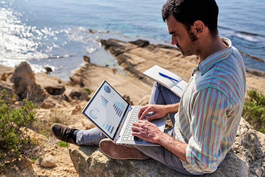 A young man works remotely with the sea in the background