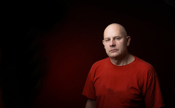 Studio portrait of middle-aged man serious face looking at camera isolated on dark red light background