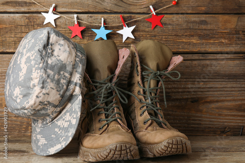 Military uniform and stars in colors of USA flag on wooden background
