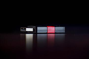 pendrive o memoria de color negro y rojo reflejándose sobre una plataforma negra