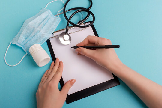 Top view of woman hands with pen over paper on folder isolated on blue background. Stethoscope, pills bottle and surgery mask on blue. Doctor fills out a form on paper for analyzes.
