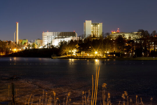 Nightly view of Meilahti district in Helsinki with illuminated white buildings casting reflections on the water surface.