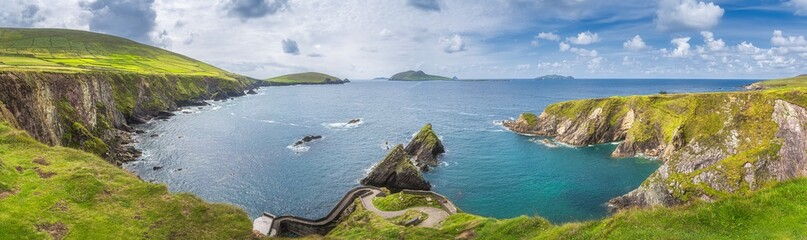 Beautiful panoramic shot of amazing Dunquin Pier and harbour with tall cliffs, turquoise water and...