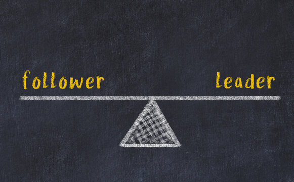 Concept of balance between follower and leader. Chalk scales and words on it