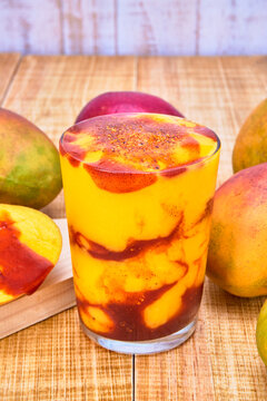 chamoyada or mango smoothie with chamoy, a mexican refreshing drink. served with mangoes with chamoy on a wooden table with a white wooden plank background.