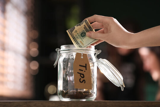 Woman putting tips into glass jar on wooden table indoors, closeup