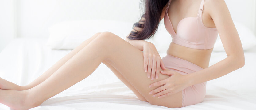 Beautiful young asian woman touch skin leg smooth with cream and lotion for hydration and smooth, girl applying body care and cosmetic, beauty perfect with wellness, health and care, banner website.