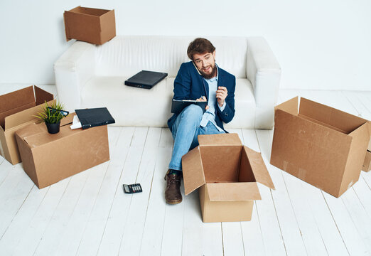 Business man near boxes with things unpacking moving to a new location office official lifestyle