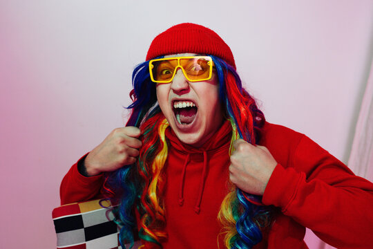 Expressive bizzare emotional man in silly colorful outfit shouting out of loud.