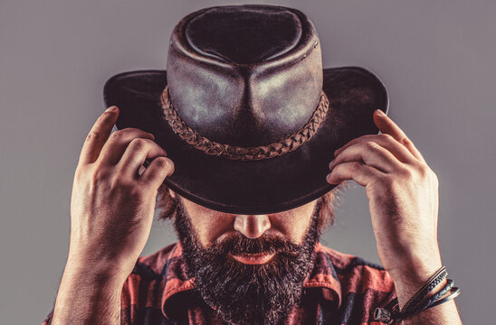American cowboy. Leather Cowboy Hat. Portrait of young man wearing cowboy hat. Cowboys in hat. Handsome bearded macho. Man unshaven cowboys
