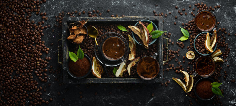 Mushroom Chaga Coffee Superfood, trendy drink on a black stone background. Top view. Free space for text.
