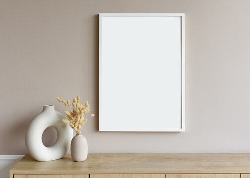 Blank picture frame mockup on gray wall. White living room design. View of modern scandinavian style interior with artwork mock up on wall. Home staging and minimalism concept