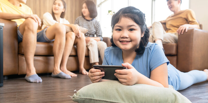 asian daughter child concentrate focus hand use smartphone game online playing with cheerful and fun quarantine stay home in living room home interior background