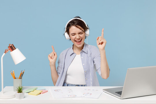 Young secretary employee business woman in casual shirt sit work at white office desk with pc laptop wearing headphones listen to music resting during break isolated on pastel blue background studio.