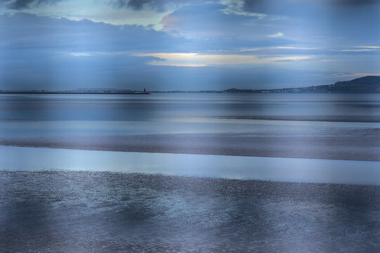 Beautiful evening view of Blackrock Beach during low tide seen from the train station through metal fence, Dublin Ireland. Creative blur