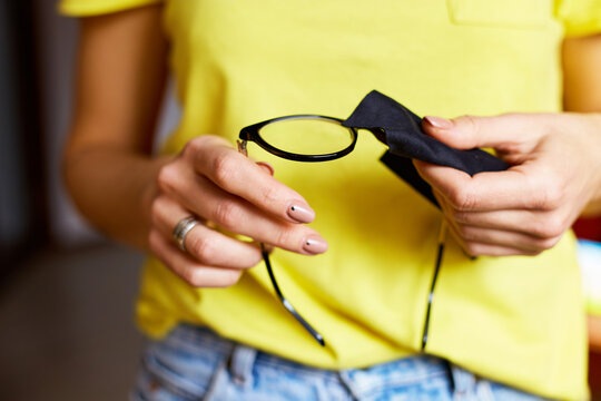 Close up crop hands of woman wiping trendy black glasses lens with towel, black microfiber tissue, female in yellow t-shirts and jeans, copy space. Healthcare, vision and medicine concept