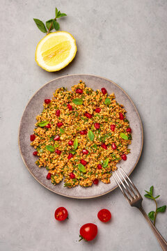 Kisir on gray plate on concrete table top. Turkish cuisine bulgur and parsley salad dish with pomegranate. Turkish food and meal. Top view.