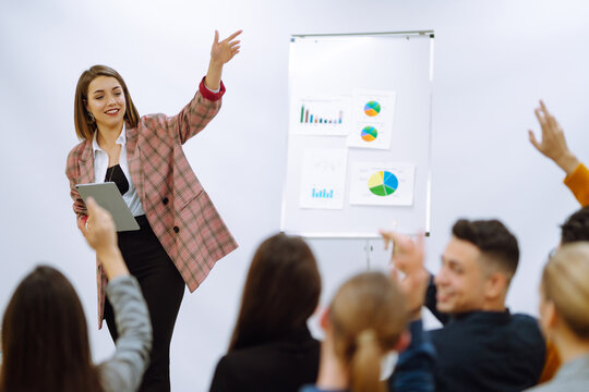 Young woman coach speaker giving flipchart presentation, speaker leading training, mentor leader explain strategy schedule at team meeting. Planning, analysis, collaborate work in teamwork.