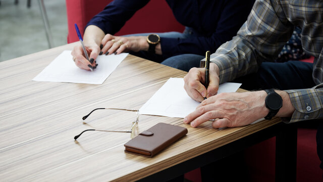 An adult woman and a man, sitting at a table in the office, fill out documents or forms. The concept of a marriage contract, agreement or divorce proceedings