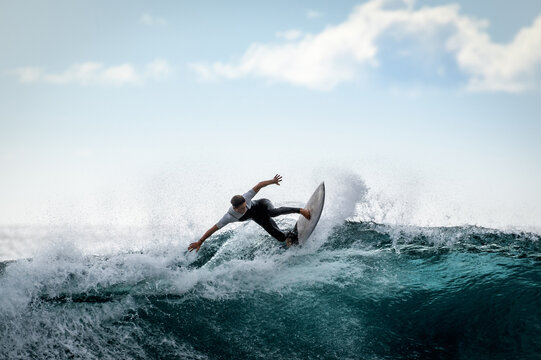 Young surfer with with wetsuit enjoying big waves in Tenerife, Canary Islands. Sporty boy riding his surf board on the ocean wave. Brave teenager making tricks on the rough sea during a competition.